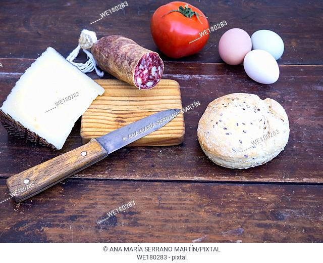 An Iberian pork sausage on an old wooden board with an antique knife, a loaf of Spanish rustic seed bread, cheese, one tomato and three multicolor eggs