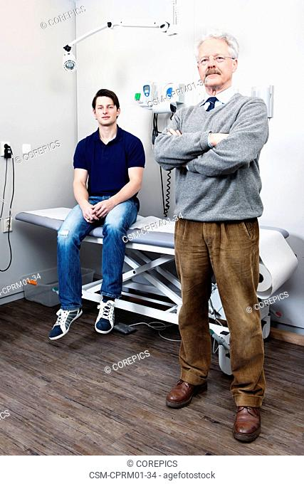 Elderly doctor posing in front of his practice where one of his patients is sitting on the examination table