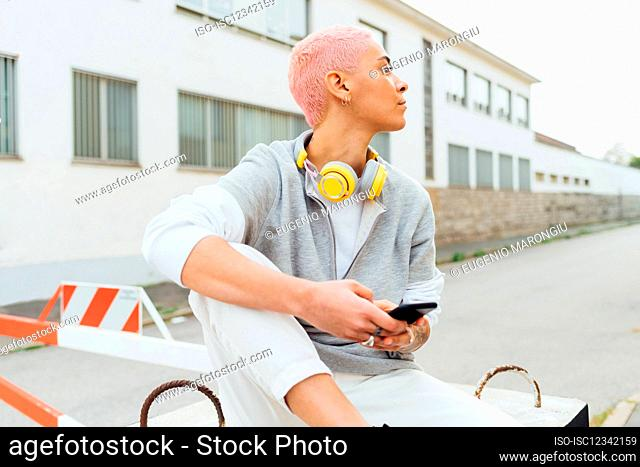 Young woman using cellphone, looking away