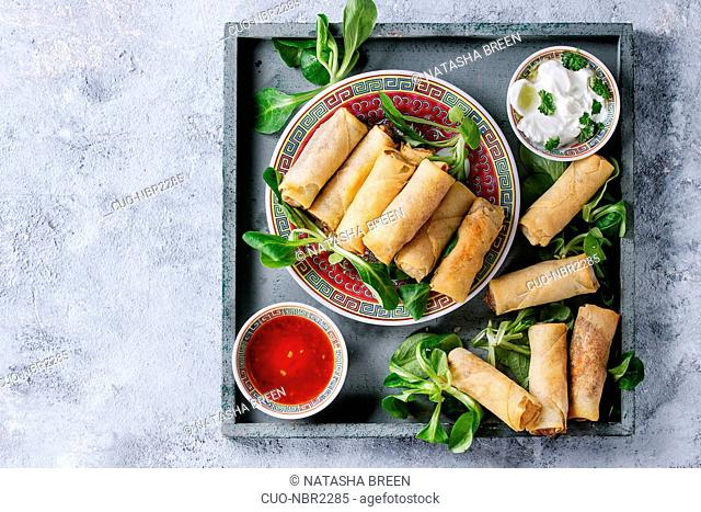 Fried spring rolls with red and white sauces, served in china plate on square wood tray with fresh green salad over gray blue texture background