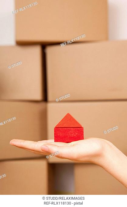 Hand holding model house Cardboard boxes moving in
