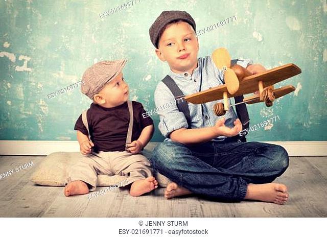 zwei Brüder spielen mit Holzflieger