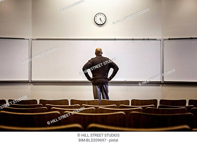 Professor standing in empty classroom