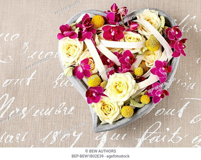 Floral arrangement with roses and orchids in heart shape. Party decoration
