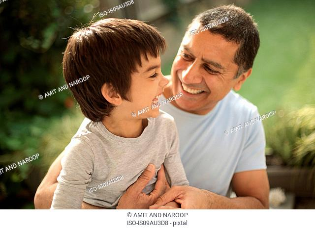 Boy sitting on father's lap, face to face laughing