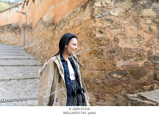 Spain, Granada, smiling young woman with camera at the Alhambra