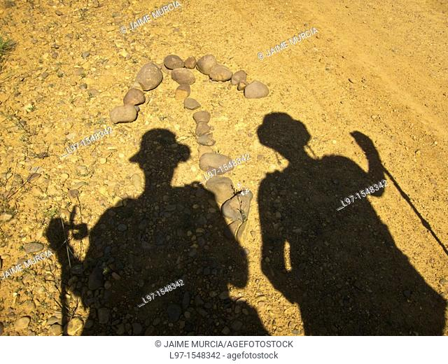 Silhouette of two walkers over stone arrow pointing the way along the Camino de Santiago