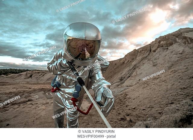 Spaceman on a nameless planet, probing soil
