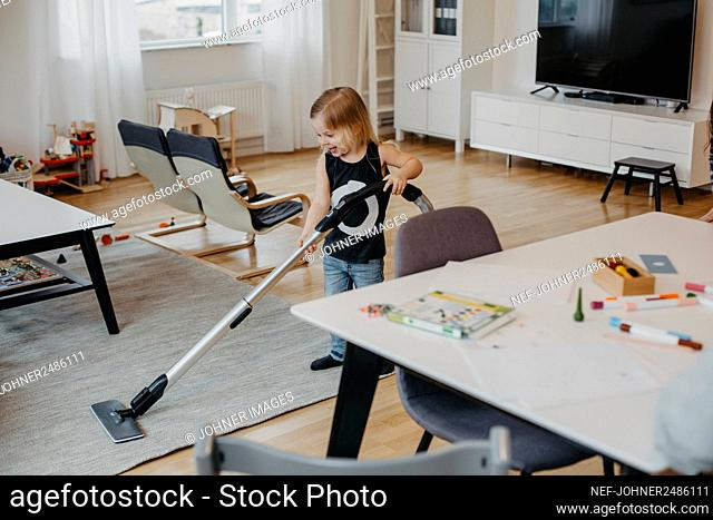 Smiling girl vacuum cleaning living room