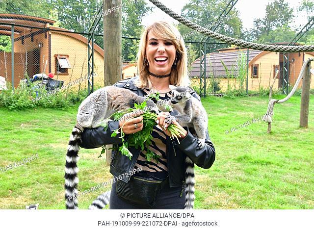 07 September 2019, Germany (German), Hodenhagen: Annemarie Eilfeld in the Serengeti-Park Hodenhagen caresses and feeds calicoes