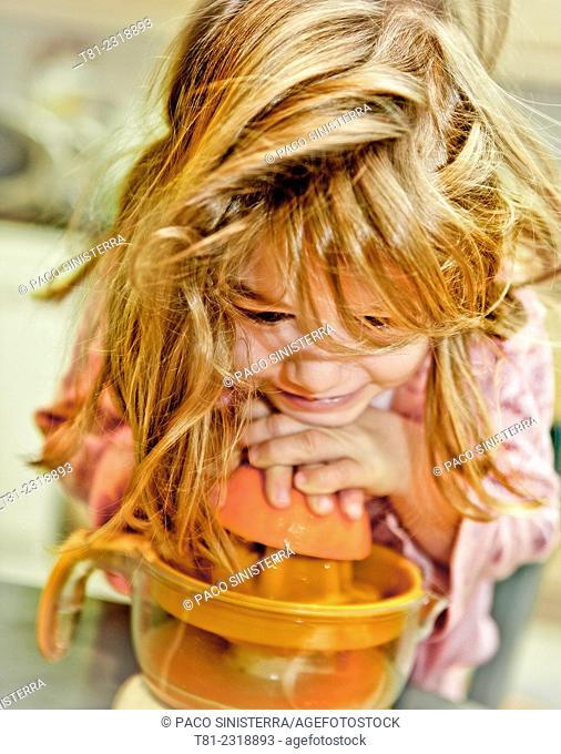 Girl squeezing oranges in Valencia, Spain