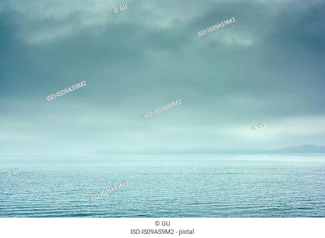 View of horizon over calm water with dramatic stormy sky