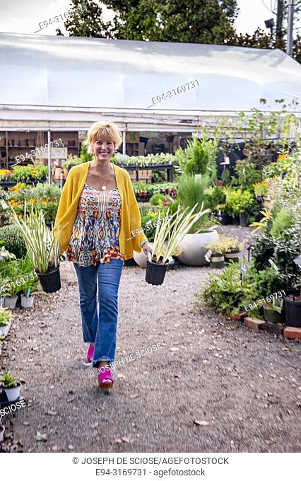 A pretty 42 year old blond woman shopping at a garden store carrying 2 potted iris ensata plants