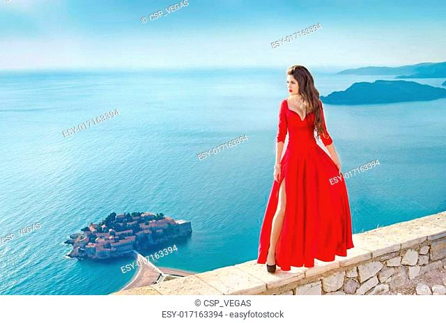 Beautiful Fashion Girl model in gorgeous red dress over the sea