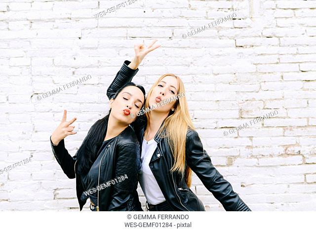 Two young women pouting mouth and showing victory sign in front of white brick wall