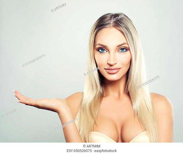 Smiling Woman Spa Model with Healthy Skin and Blonde Hair Showing Empty Copy Space on the Open Hand on White Background. Facial Treatment