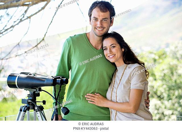 Portrait of a couple smiling beside a binoculars on tripod