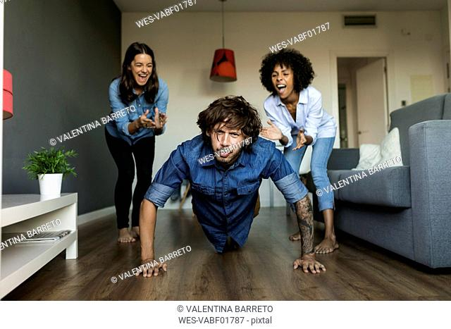 Two women encouraging man doing pushups at home