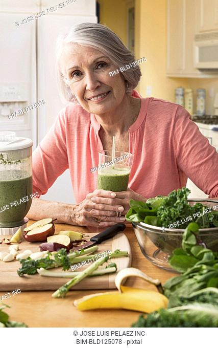 Senior Caucasian woman drinking green smoothie