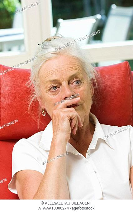 Elderly lady being deep in thought