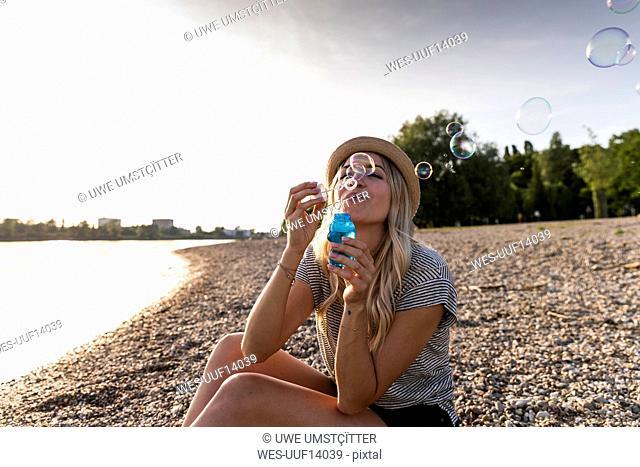 Blond woman blowing soap bubbles at riverside