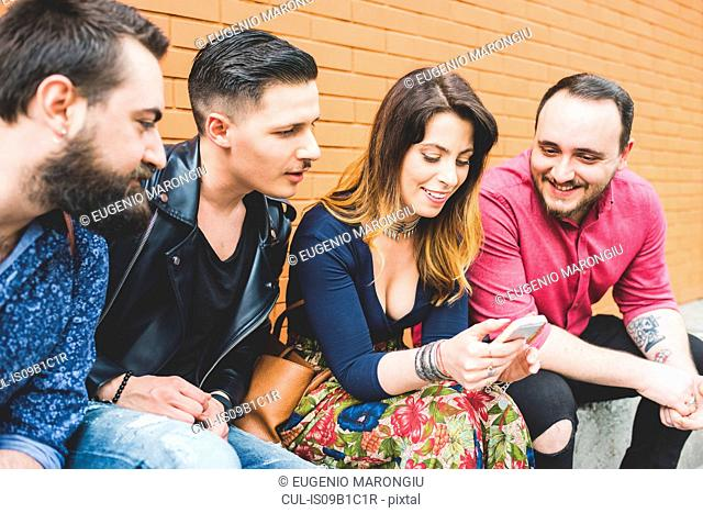Group of friends looking at message on cellphone