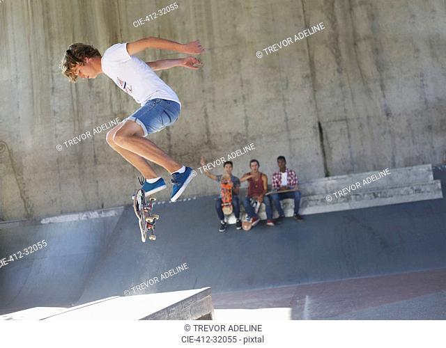 Teenage boy flipping skateboard at skate park