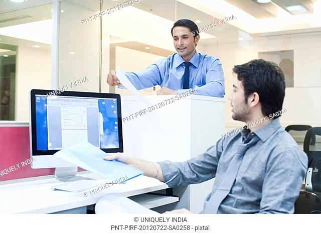 Two businessmen working in a office and smiling