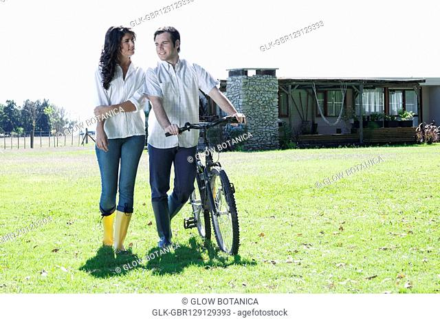 Couple walking with a bicycle and smiling