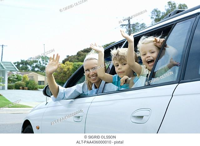 Mother and two children waving out of car windows, looking at camera