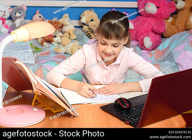 in the children's room sits a girl at a desk and makes a homemade