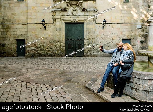 Couple taking selfie with smartphone at Sant Felip Neri Square, Barcelona, Spain
