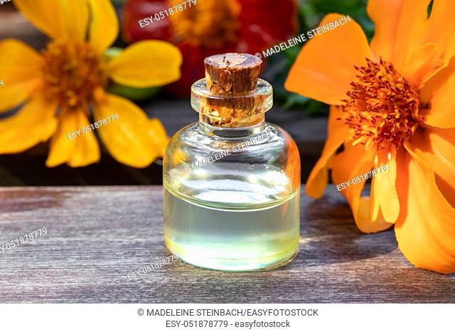 A bottle of essential oil with fresh Tagetes patula flowers