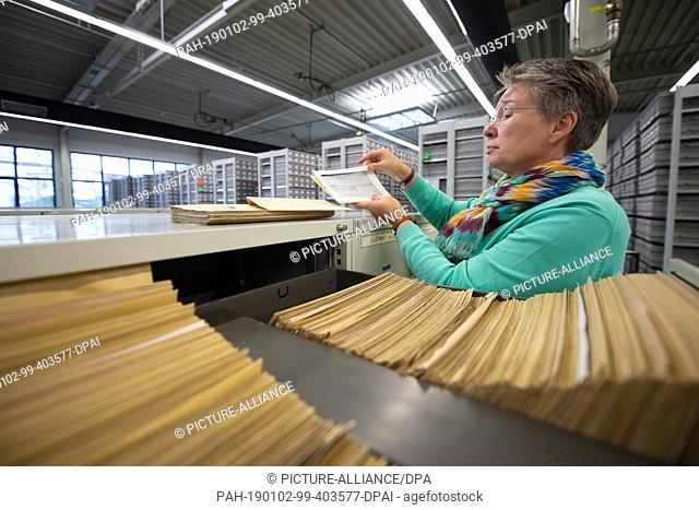 11 December 2018, Hessen, Bad Arolsen: Nicole Dominicus, Head of Archive Administration, holds maps of the Central Name Index (ZNK) at a file cabinet in the...
