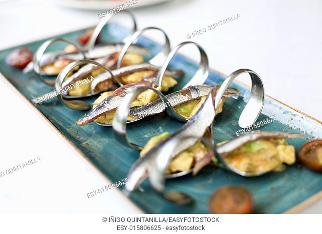 still life of ceramic green dish tray with delicious anchovies with guacamole and tomato in metal curved spoons on restaurant white table