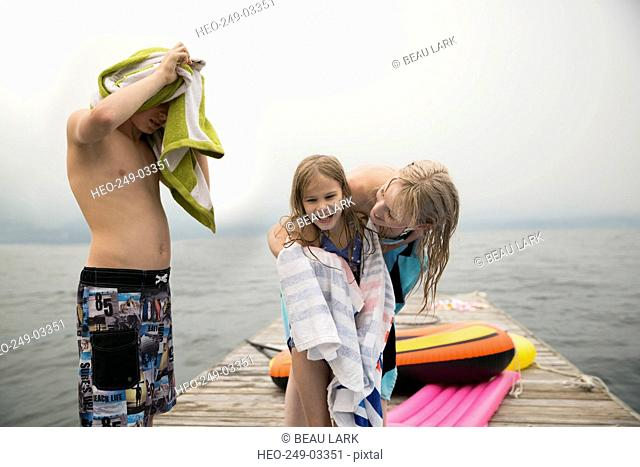 Mother wrapping towel around daughter on lake dock