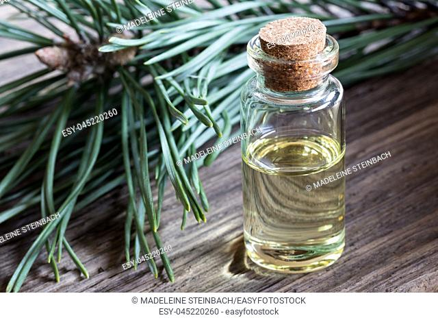 A bottle of pine essential oil with pine branches in the background