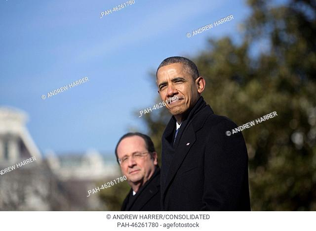 United States President Barack Obama (R) and President Francois Hollande of France listen to the national anthems during an arrival ceremony on the South Lawn...