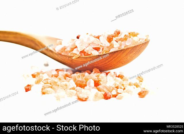 Pink himalayan salt in wooden spoon isolated on white background