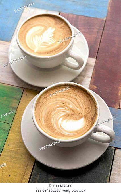Two Cups of coffee with latte art on wooden table