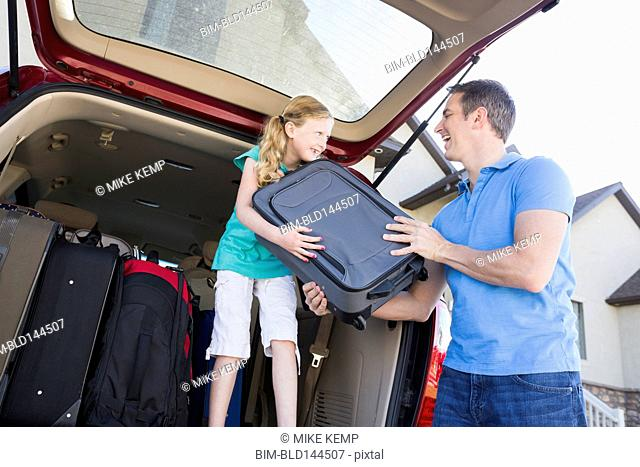 Caucasian father and daughter unpacking suitcases from car
