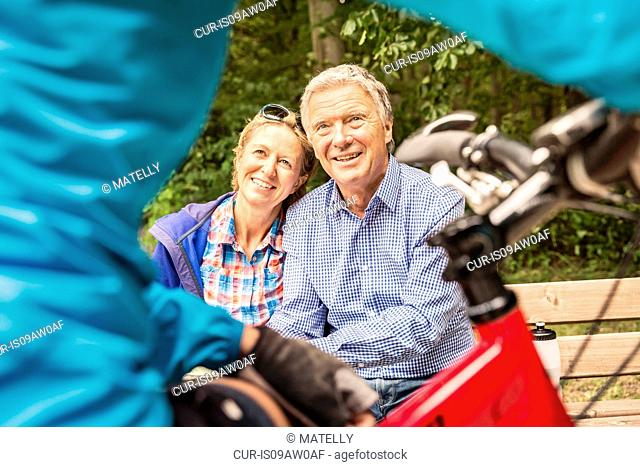 Cropped shot of mountain biker chatting to couple on park bench