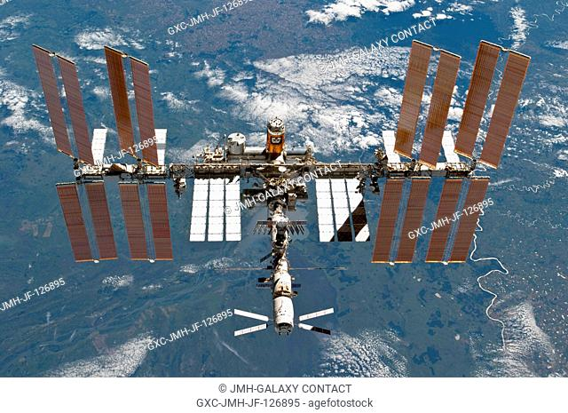The International Space Station is featured in this image photographed by an STS-133 crew member on space shuttle Discovery after the station and shuttle began...