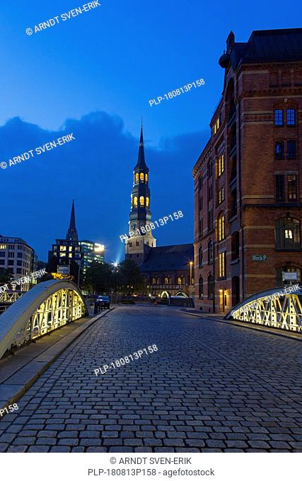 Bridge with cobblestones and Hauptkirche Sankt Katharinen at night, Speicherstadt, district in the Hafencity quarter, port of Hamburg, Germany