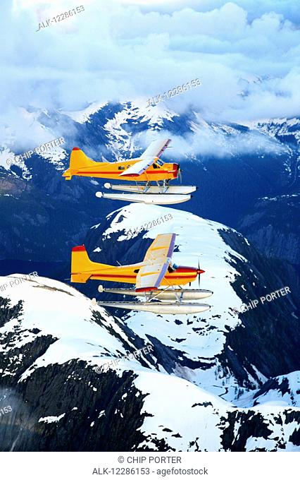 Cessna 185 flying in front of a DeHavilland Beaver and flying over rugged mountains of the Misty Fjords National Monument Wilderness, Spring