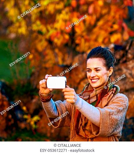 Smiling young brunette woman taking photo with mobile phone while relaxing in beautiful evening in autumn park
