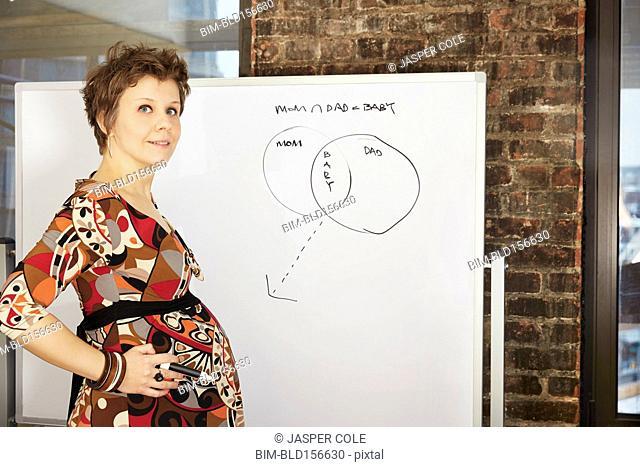Pregnant businesswoman standing near whiteboard in office