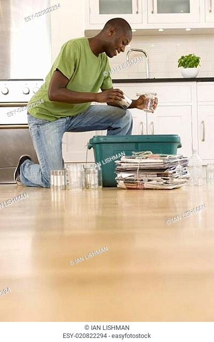 Young man putting can and glass jar into recycling bin in kitchen, ground view