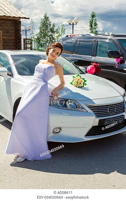 Bride in white wedding dress on a background of luxury car