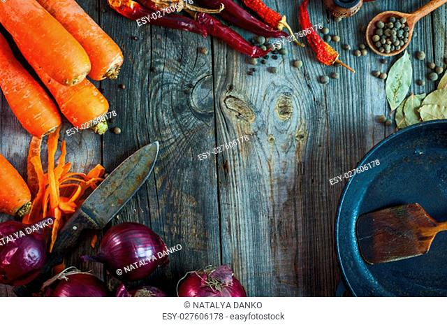 Fresh carrots and red onion with a frying pan on a gray wooden surface, top view, an empty space in the middle